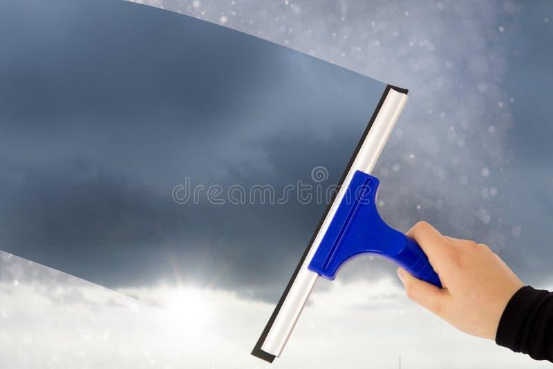 Vrouwen schoonmakend venster met rubberschuiver stock foto