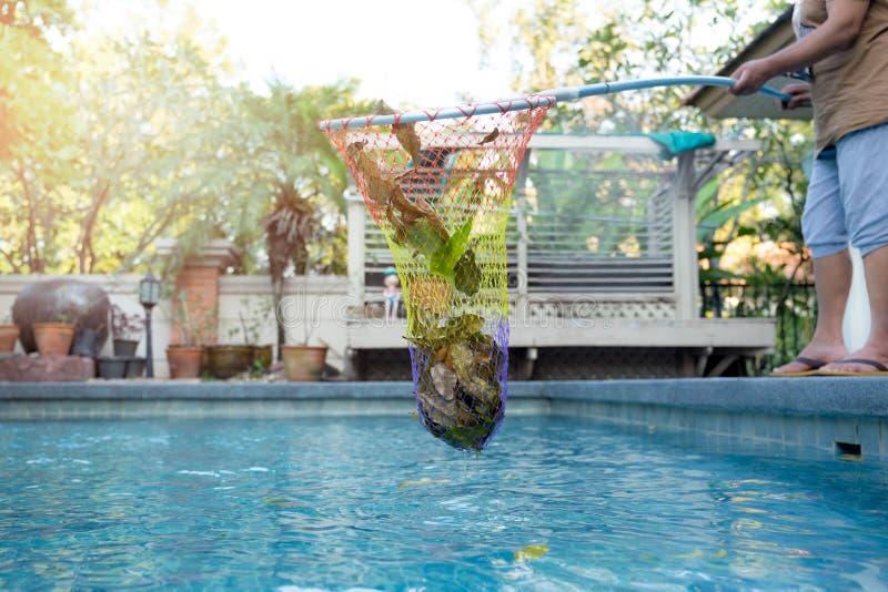 Vrouwen schoonmakend zwembad van gevallen bladeren met netto royalty-vrije stock fotografie