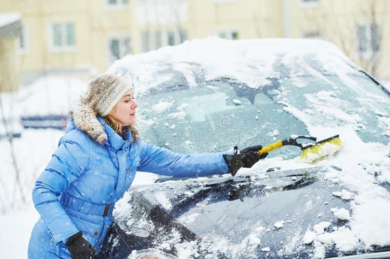 Vrouwen schoonmakende auto van sneeuw royalty-vrije stock foto's