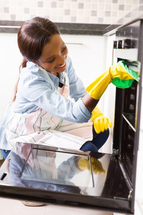 Vrouwen schoonmakende oven stock fotografie