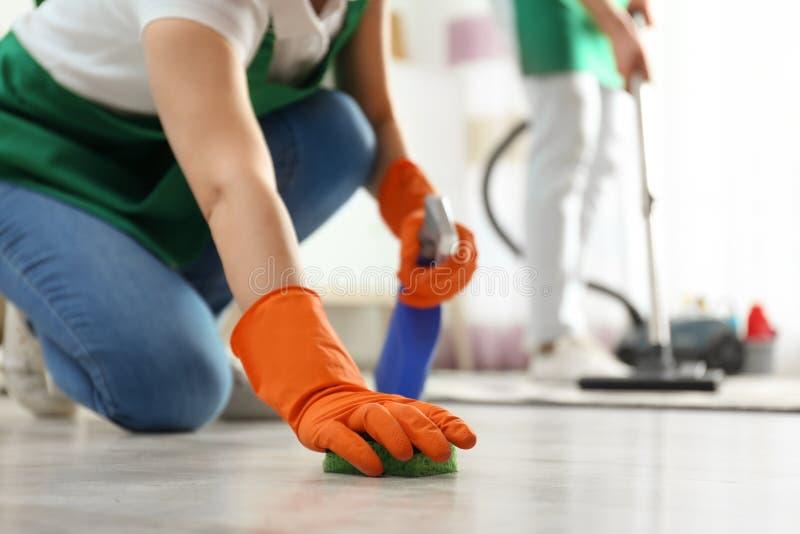 Vrouwen schoonmakende vloer met spons, close-up stock foto's