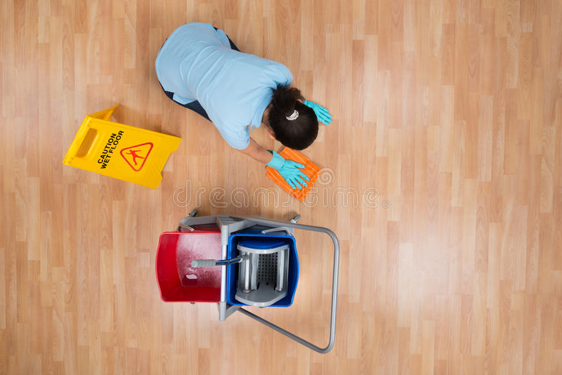 Vrouwen Schoonmakende Vloer met Vod stock foto's