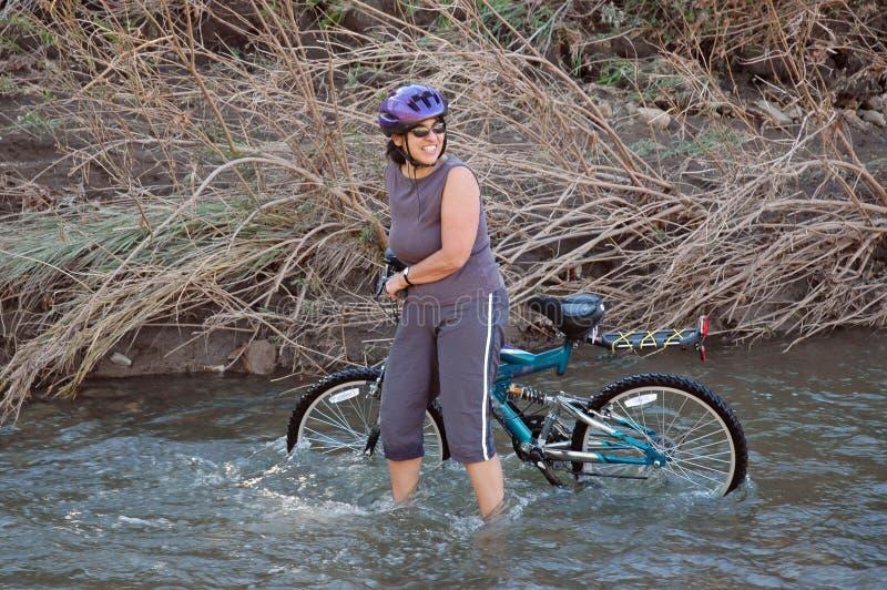 Vrouwen in stroom met fiets stock foto's