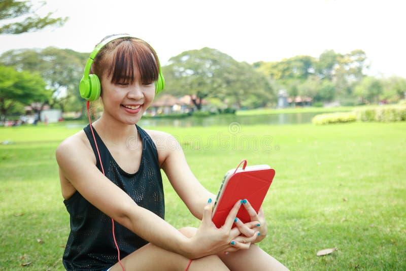 Vrouwen zitten die aan muziek in de tuin luisteren royalty-vrije stock foto's