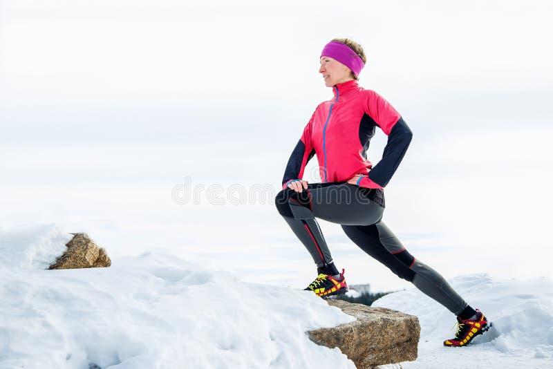 Vrouwenagent het uitrekken zich benen vóór looppas Het jonge atletenvrouw uitwerken royalty-vrije stock foto