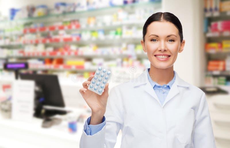 Vrouwenapotheker met pillendrogisterij of apotheek stock afbeeldingen