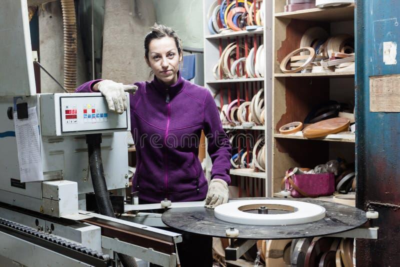 Vrouwenarbeider die randmachine met behulp van om meubilair bij timmerlieden te maken royalty-vrije stock afbeelding