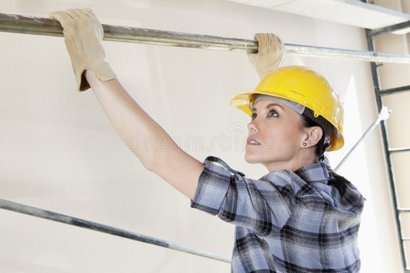 Vrouwenarbeider die staaf plaatsen op steiger bij bouwwerf stock afbeelding