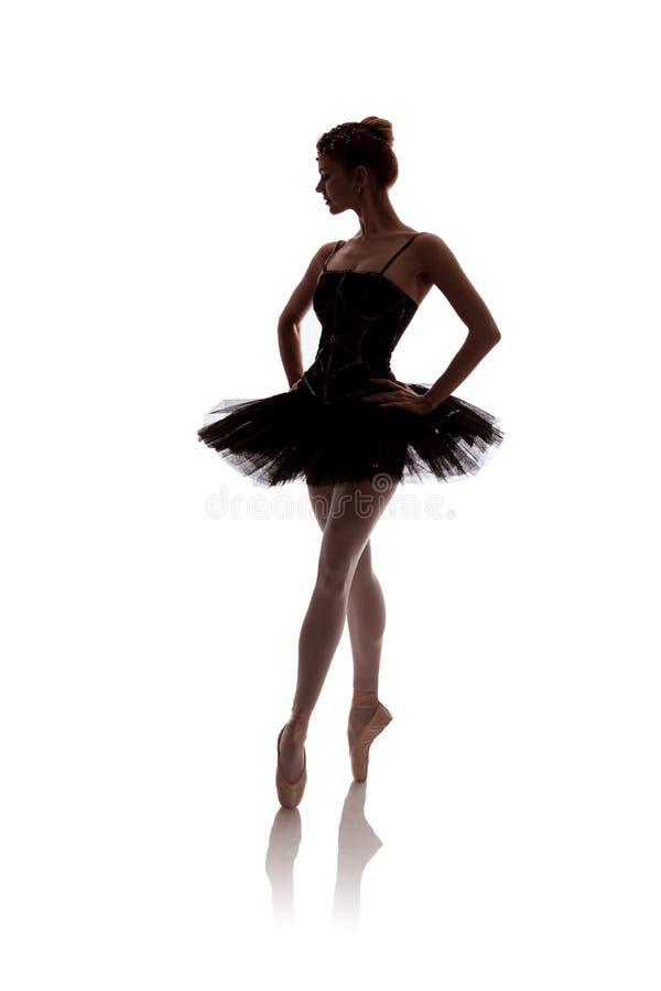 Vrouwenballerina in het zwarte paktutu stellen op witte achtergrond stock foto