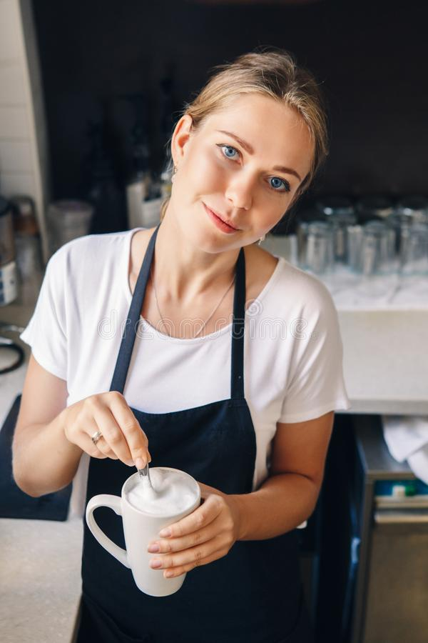 Vrouwenbarista die koffie in winkel maken royalty-vrije stock afbeeldingen