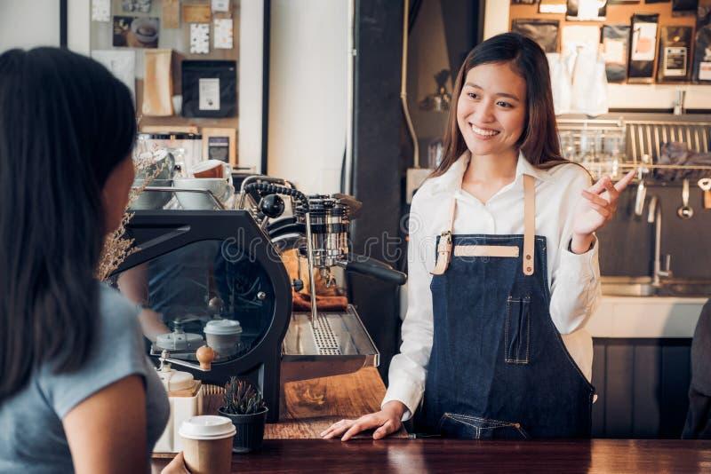Vrouwenbarista die met klant over geproeft van koffiekop met gelukkige emotie bij tegenbar bij koffie spreken de zaken van de kof royalty-vrije stock fotografie