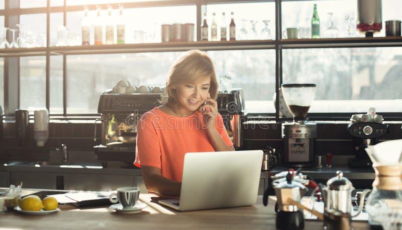 Vrouwenbarista die op middelbare leeftijd aan laptop werken en op smartphone spreken royalty-vrije stock foto's