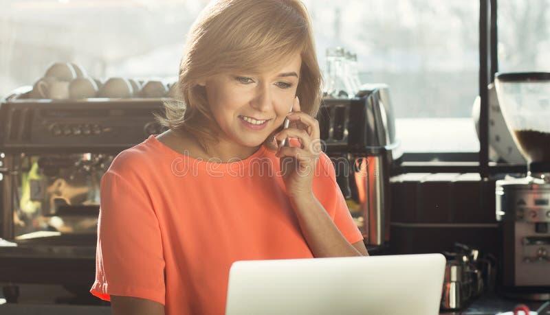 Vrouwenbarista die op middelbare leeftijd aan laptop werken en op smartphone spreken stock fotografie