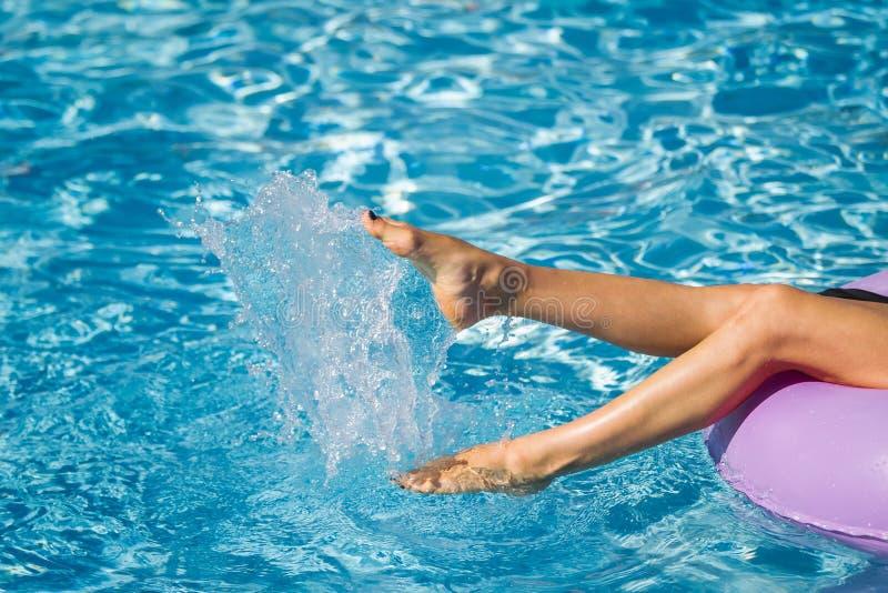 Vrouwenbenen die met water in de pool spelen stock afbeeldingen