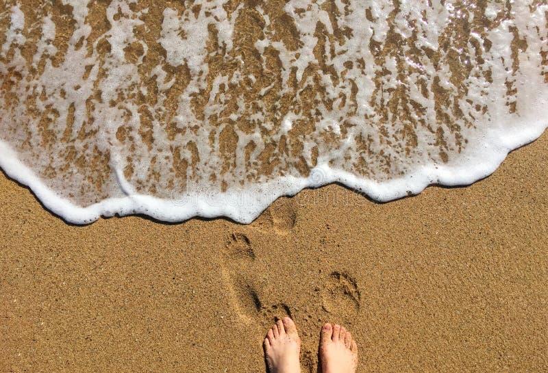 Vrouwenbenen door de kust die van een zonnige dag genieten royalty-vrije stock fotografie