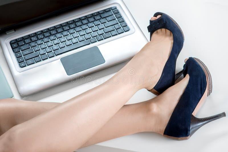 Vrouwenbenen en laptop stock afbeelding