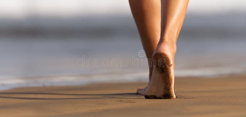 Vrouwenbenen en voeten die op het zand van het strand lopen royalty-vrije stock foto's