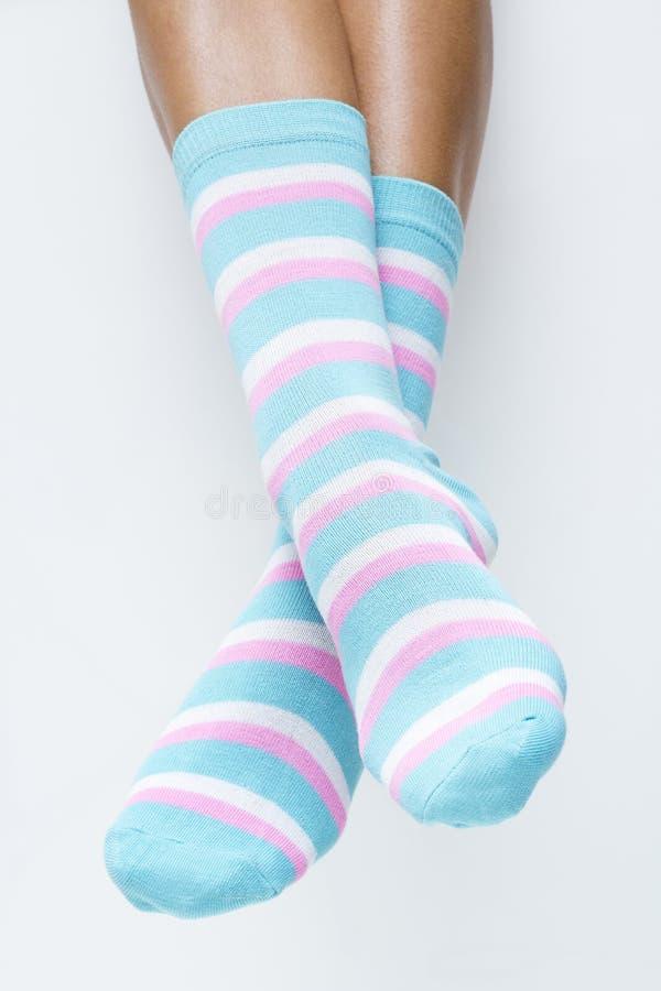 Vrouwenbenen in gestreepte sokken stock fotografie