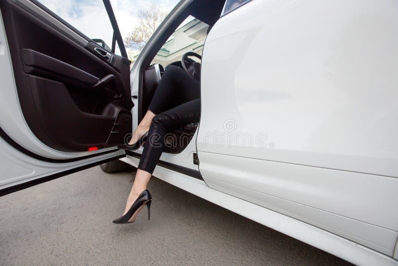Vrouwenbenen in hoge hielen bij de auto stock afbeelding