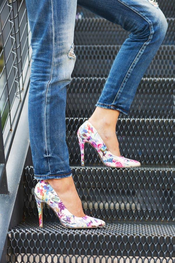 Vrouwenbenen in jeans en kleurrijke sexy hoge hielen, die zich op een trap bevinden, die van de kant wordt gefotografeerd royalty-vrije stock fotografie