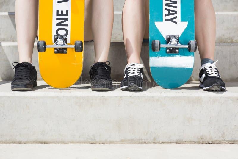 Vrouwenbenen met de skateboards stock afbeelding