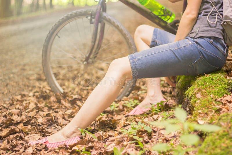 Vrouwenbenen met fiets stock afbeelding