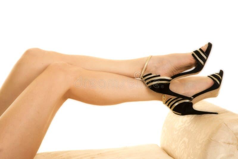 Vrouwenbenen op bank in hielen royalty-vrije stock afbeelding