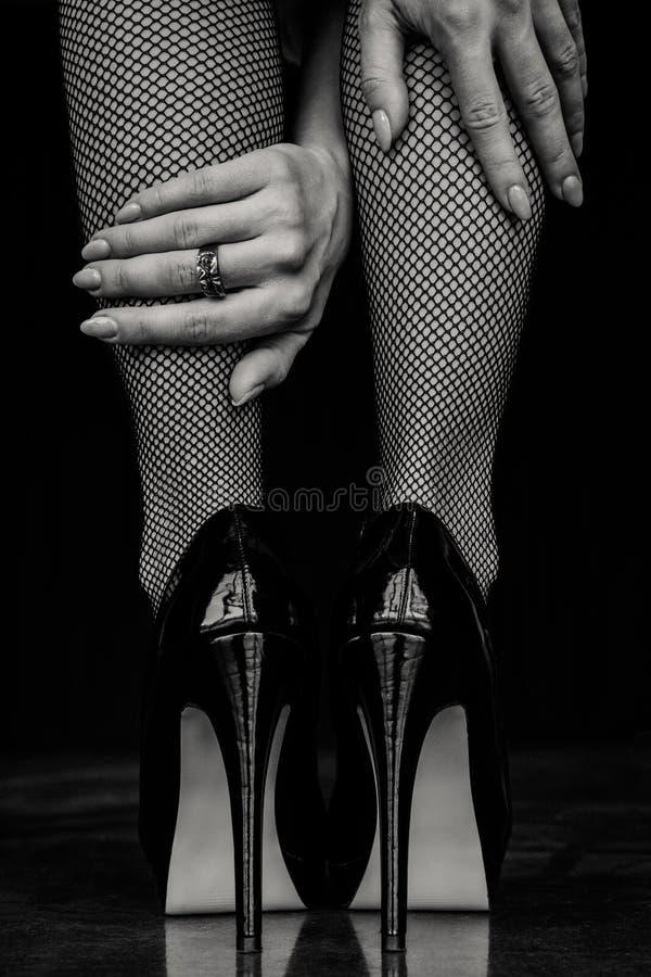 Vrouwenbenen in zwarte kousen en hoge hielenschoenen royalty-vrije stock fotografie