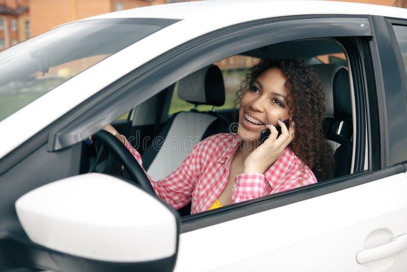 Vrouwenbestuurder die haar mobiele telefoon met behulp van terwijl het drijven van auto royalty-vrije stock afbeelding