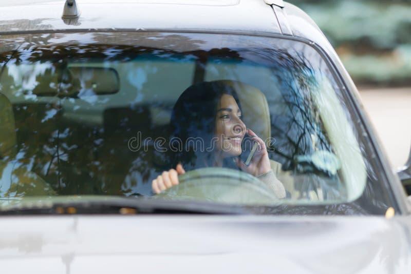 Vrouwenbestuurder die op haar mobiele telefoon spreken stock foto