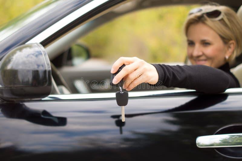 Vrouwenbestuurder met sleutels en een nieuwe auto stock afbeeldingen