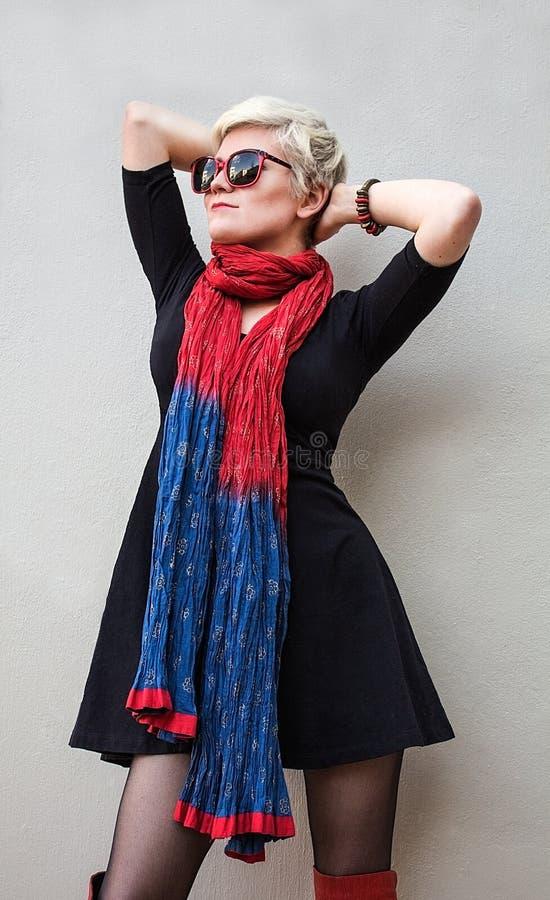 Vrouwenblonde in zwarte weinig kleding, rode sjaal, zonnebril Het Schot van de mannequin stock foto's