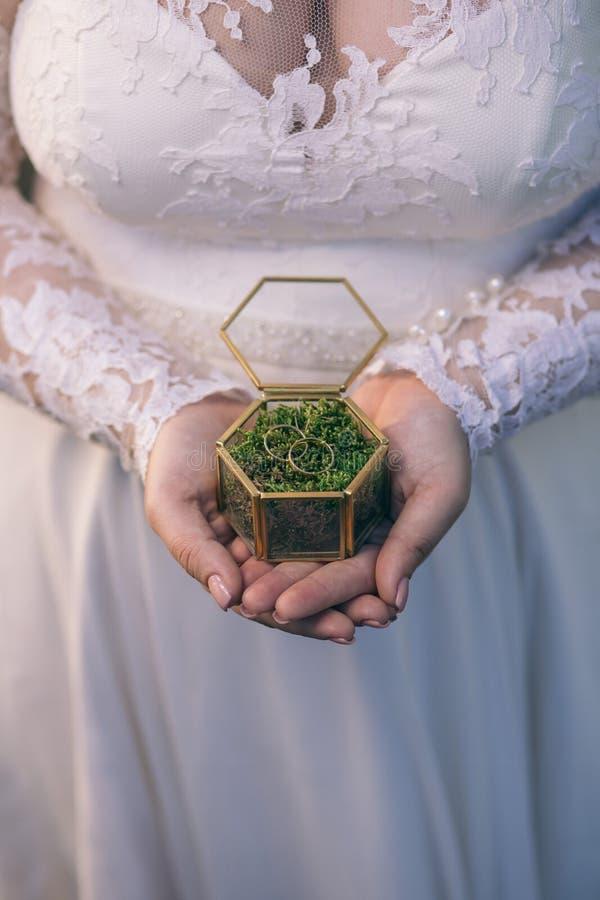 Vrouwenbruid die een doos van trouwringen houden stock foto's