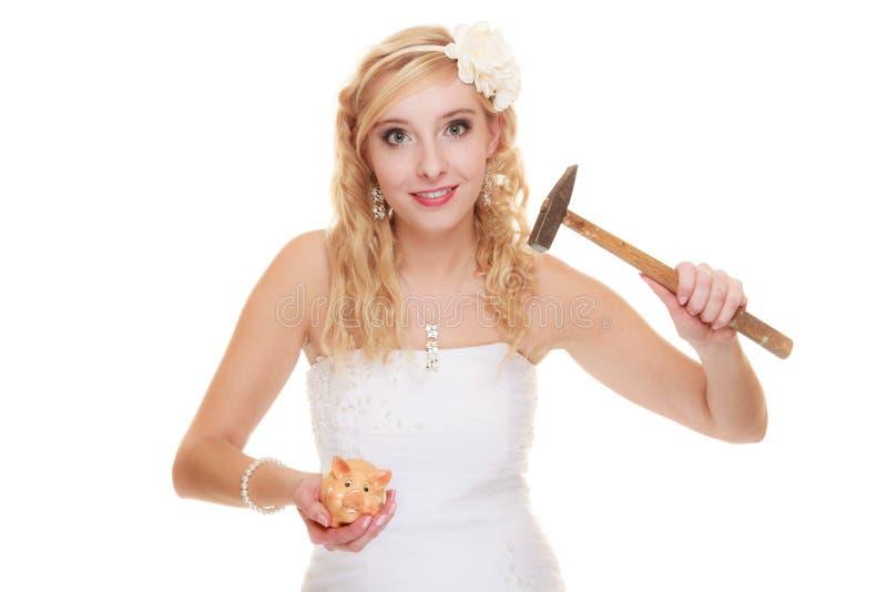 Vrouwenbruid met hamer ongeveer om spaarvarken te breken stock afbeelding