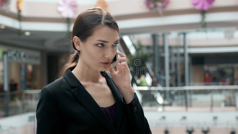 Vrouwenbrunette met telefoon die dicht omhooggaand portret glimlachen Jonge bedrijfsvrouwen professionele gelukkig Mooie multi-et royalty-vrije stock afbeelding