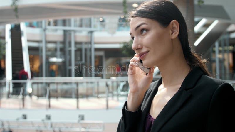 Vrouwenbrunette met telefoon die dicht omhooggaand portret glimlachen Jonge bedrijfsvrouwen professionele gelukkig Mooie multi-et stock afbeelding