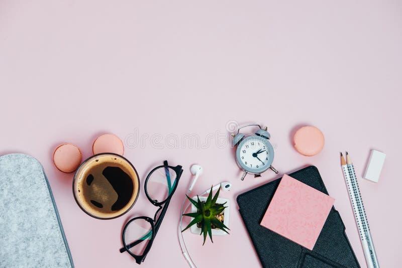 Vrouwenbureau op roze glazenblocnote het schoppen macaroo van de potlodeninstallatie stock foto's