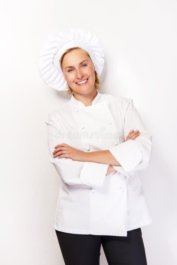 Vrouwenchef-kok die in kokuitrusting over witte achtergrond met cro glimlachen stock foto's
