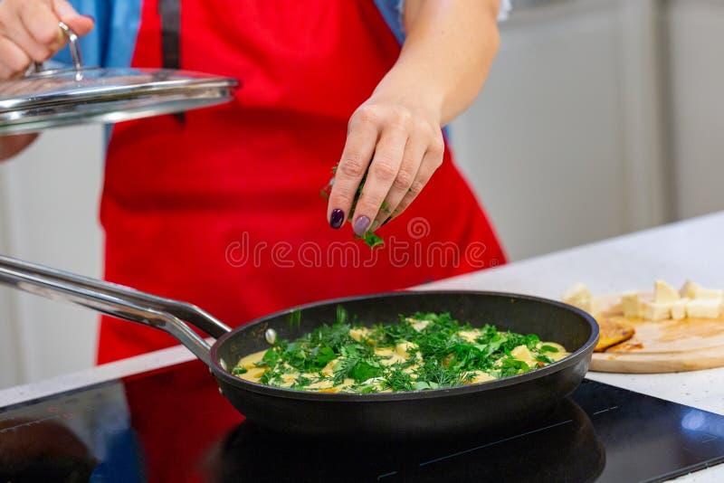 Vrouwenchef-kok die omelet met kruiden voorbereiden bij een keuken De handen sluiten omhoog stock foto