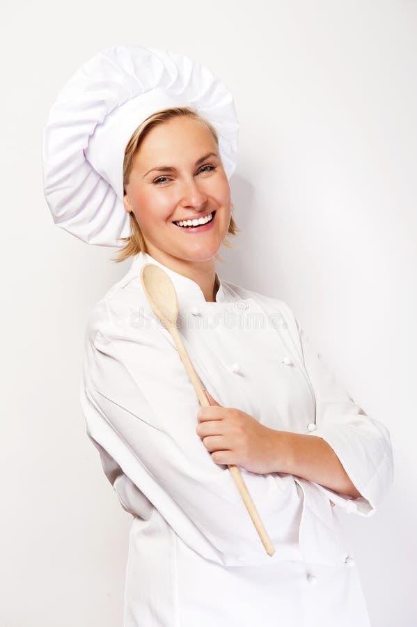 Vrouwenchef-kok in kokuitrusting die houten lepel houden en bij ca glimlachen stock afbeeldingen