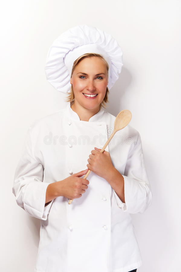 Vrouwenchef-kok in kokuitrusting die houten lepel houden en bij ca glimlachen royalty-vrije stock afbeelding