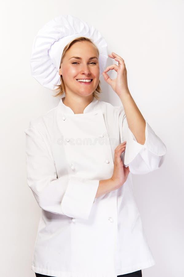 Vrouwenchef-kok in kokuitrusting die perfect teken tonen en bij ca glimlachen stock afbeelding