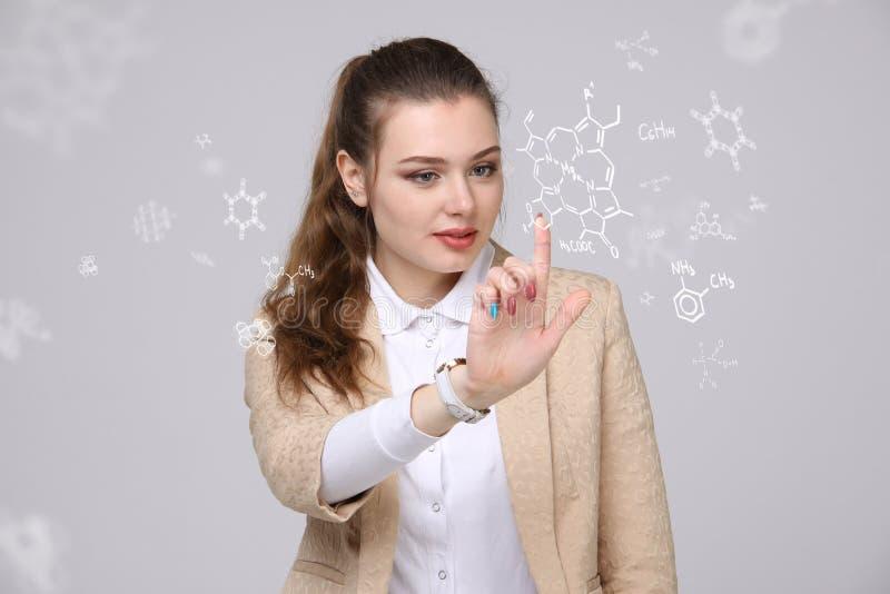 Vrouwenchemicus die met chemische formules aan grijze achtergrond werken royalty-vrije stock afbeelding