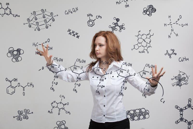Vrouwenchemicus die met chemische formules aan grijze achtergrond werken royalty-vrije stock foto