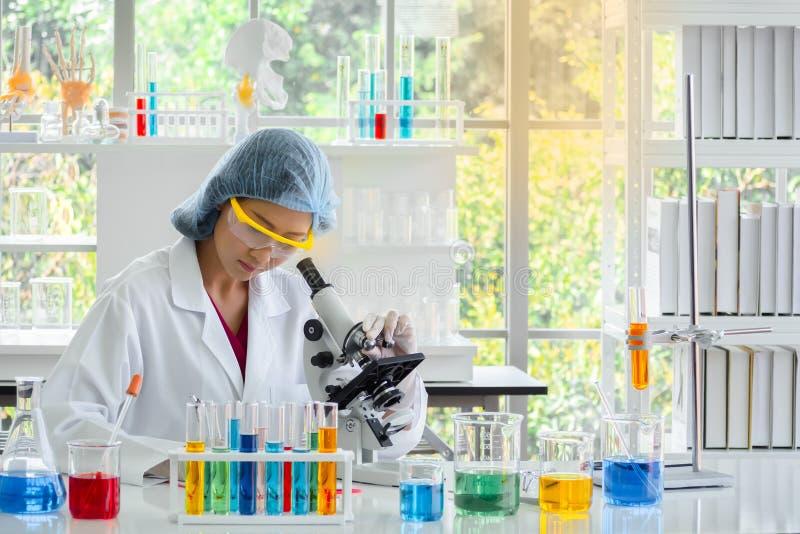 Vrouwenchemicus die microscoop gebruiken stock foto