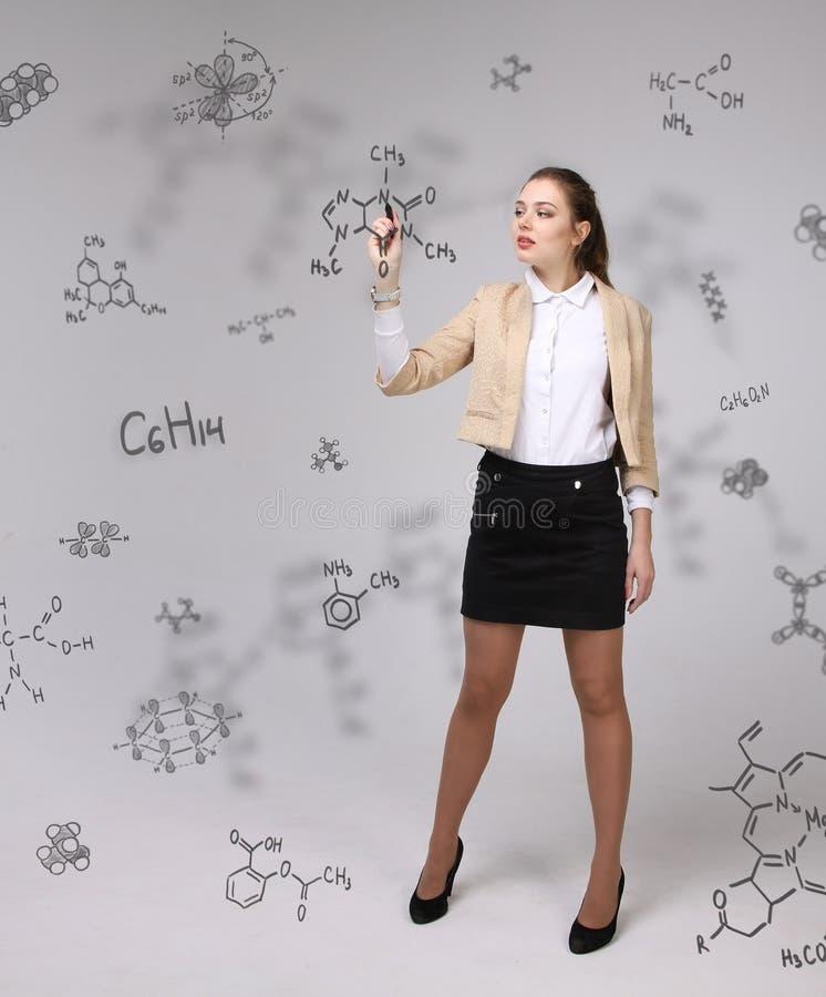 Vrouwenchemicus met naald of pen die chemische formules op grijze achtergrond schrijven stock afbeelding