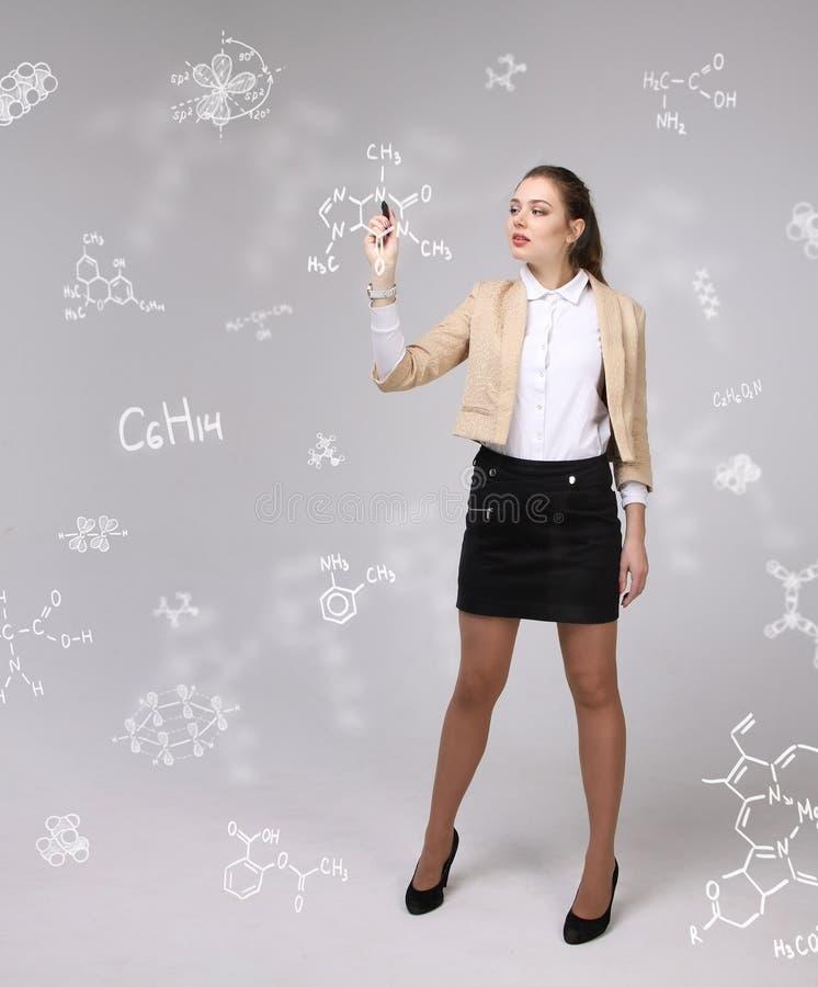 Vrouwenchemicus met naald of pen die met chemische formules aan grijze achtergrond werkt stock foto's