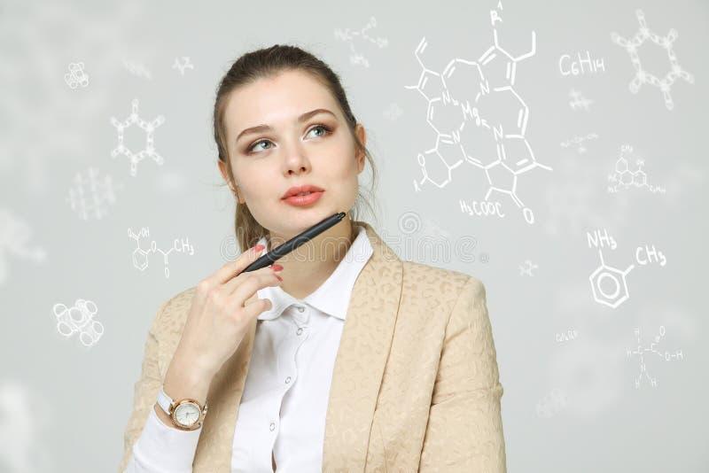 Vrouwenchemicus met naald of pen die met chemische formules aan grijze achtergrond werkt royalty-vrije stock foto's