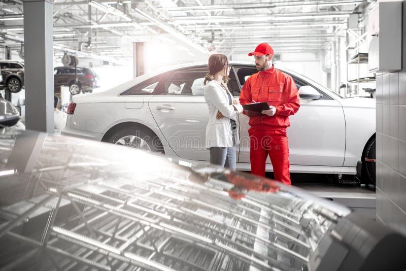Vrouwencliënt met autowerktuigkundige bij de autodienst stock foto's