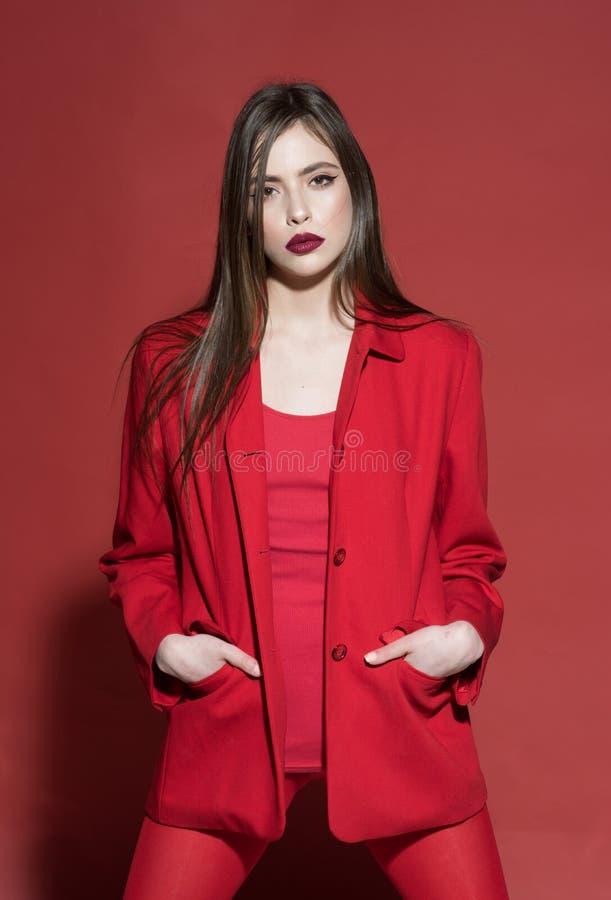 Vrouwenconcept Mooie vrouw in rode kleren Vrouw met make-up en lang haar De maniervrouw kleedde zich met stijl Vind uw stock fotografie